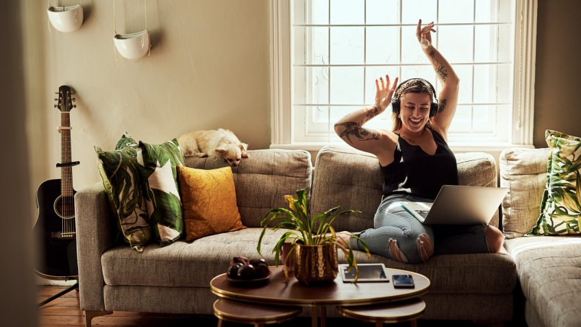 Shot of a young woman using a laptop and headphones on the sofa at home.