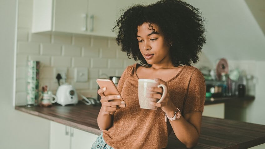 Shot of a young woman using a smartphone and having coffee in the kitchen at home.