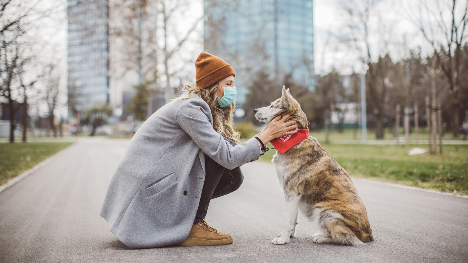 Woman during pandemic isolation walking with her dog in park.