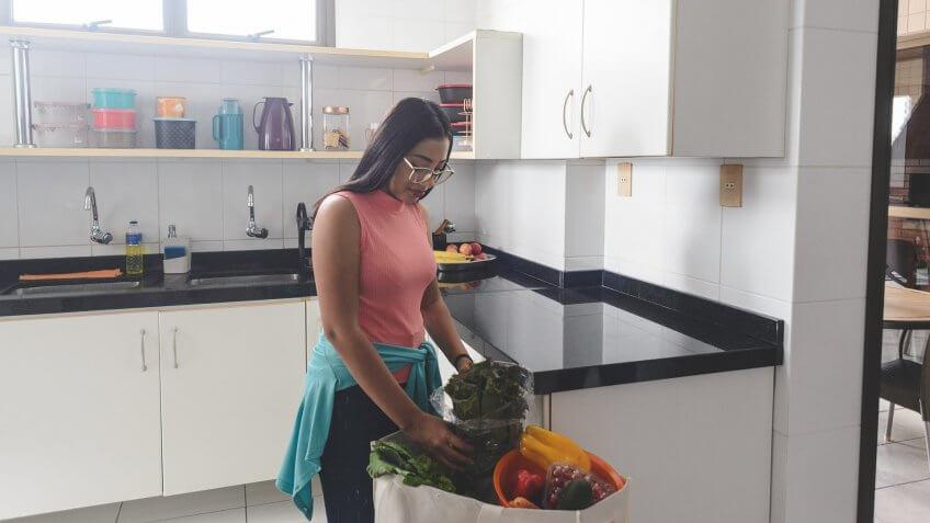 Young woman unpacking groceries from her reusable shopping bag in the kitchen.