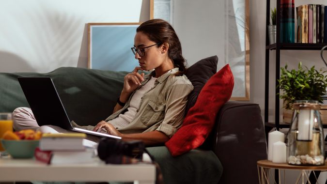 Young woman with glasses using her laptop while lying on a couch in her living room.