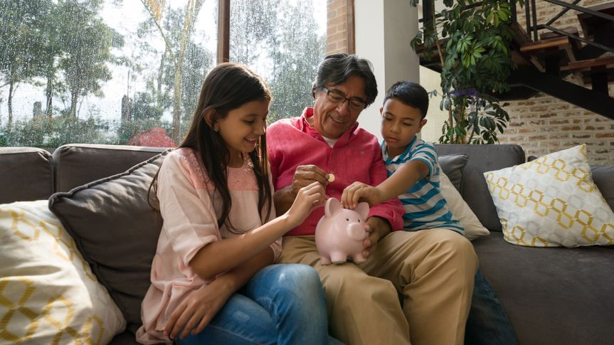 Grandfather teaching his grandkids to save money in piggy bank while sitting on couch at home all smiling.