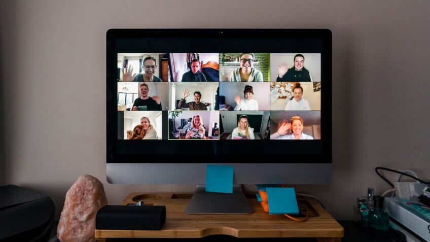 Image of a team conference call on a computer screen in a home office.