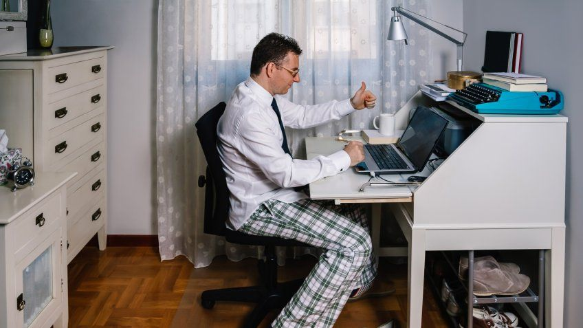 Man working from home with laptop wearing shirt, tie and pajama pants.