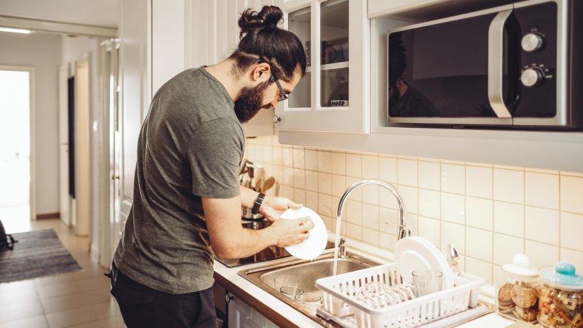 Young man washing dishes at home.