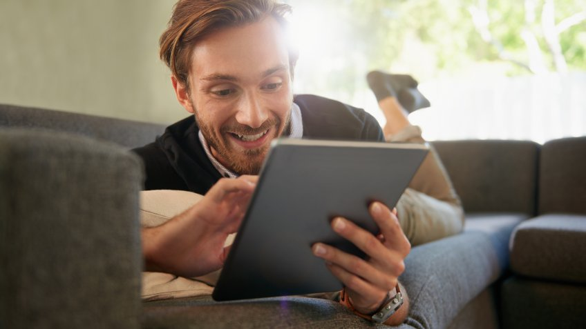 Full length shot of a handsome young man using a digital tablet while relaxing at home.