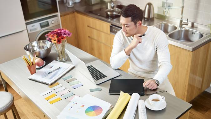 high angle view of a young asian designer sitting at kitchen counter working on a design using laptop computer and digital pen tablet.