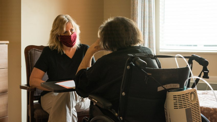 Blond female healthcare worker wearing scrubs, gloves and a red fabric face mask sits across from a patient on oxygen sitting in a wheelchair during a speech therapy session amid the corona virus COVID-19 pandemic.