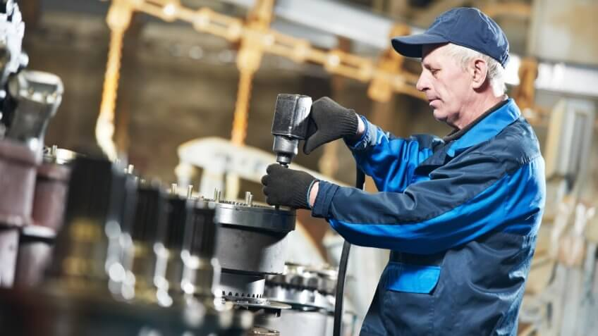 adult experienced industrial worker during heavy industry machinery assembling on production line manufacturing workshopClick on banner below to view more images in the.