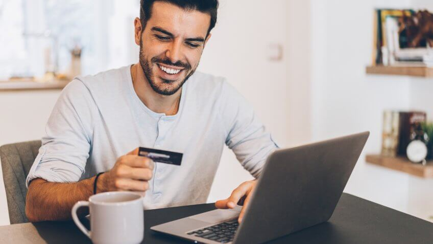 Young handsome man shopping online with credit card and laptop at home.