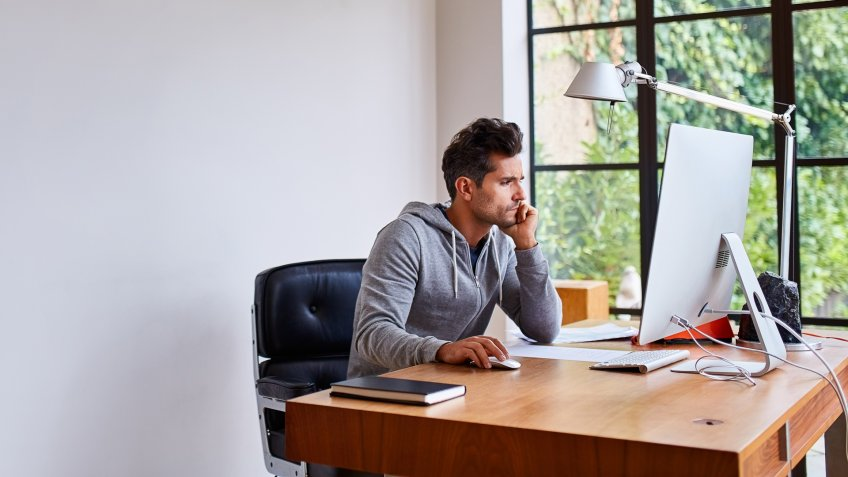 Shot of a young man working on a computer while sitting at a desk in his home office.