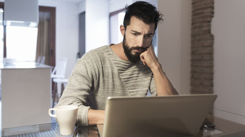 Man working at home with laptop computer.