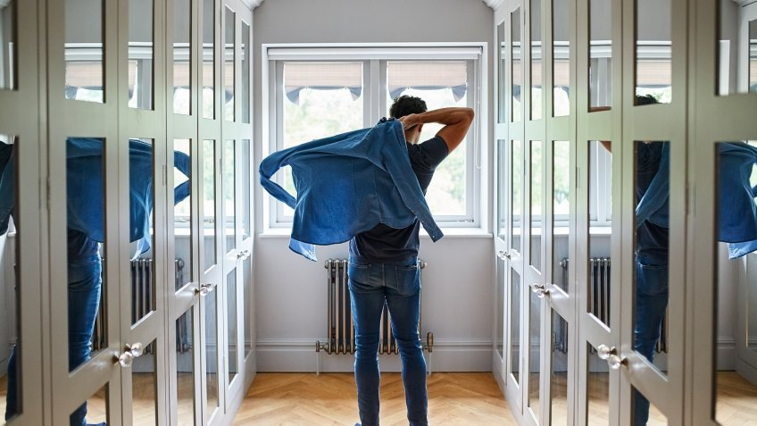 Shot of a man getting dressed in a long walk in closet full of mirrors.