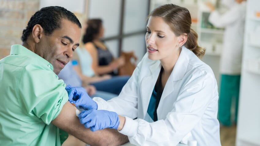 Confident mid adult Caucasian female healthcare professional gently places a bandage on a mature male patient's arm.