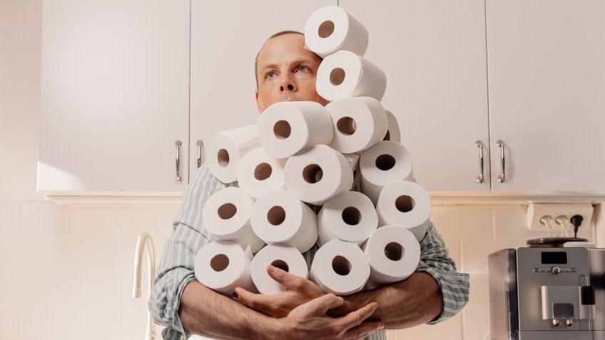 Man hoarding toilet paper holding many rollsPhoto taken indoors in kitchen of person holding toilet paper.