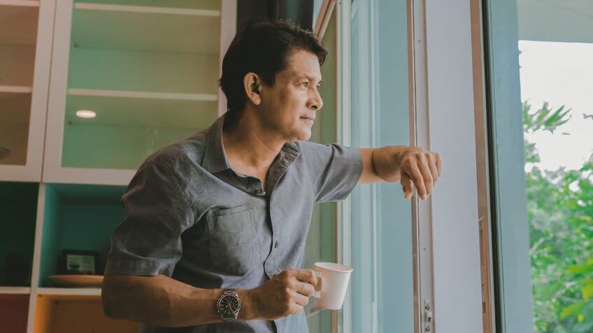 Middle-aged Asian man looking through a window, sipping coffee and using ideas.