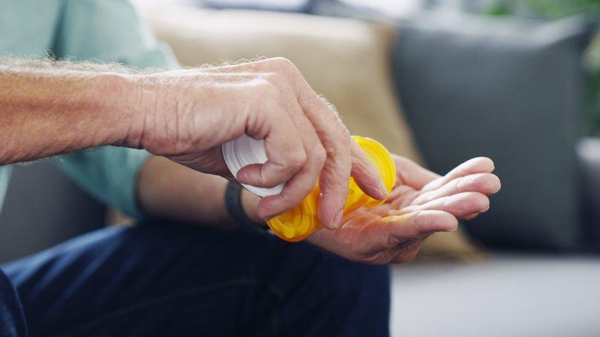 Shot of an unrecognisable senior man taking medication at home.