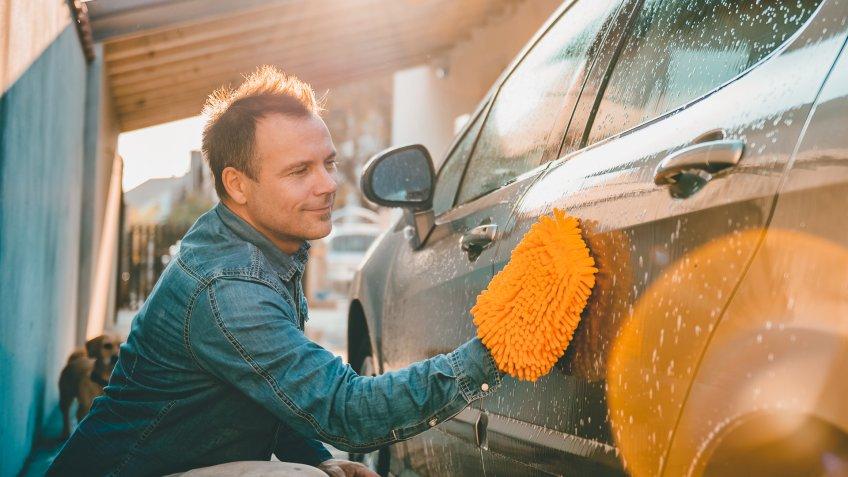 man washing his car at his house with his dog