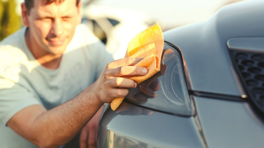 close up of man cleaning car with microfiber cloth, car detailingYoung man washing car -Car wash process with water and washing foam.