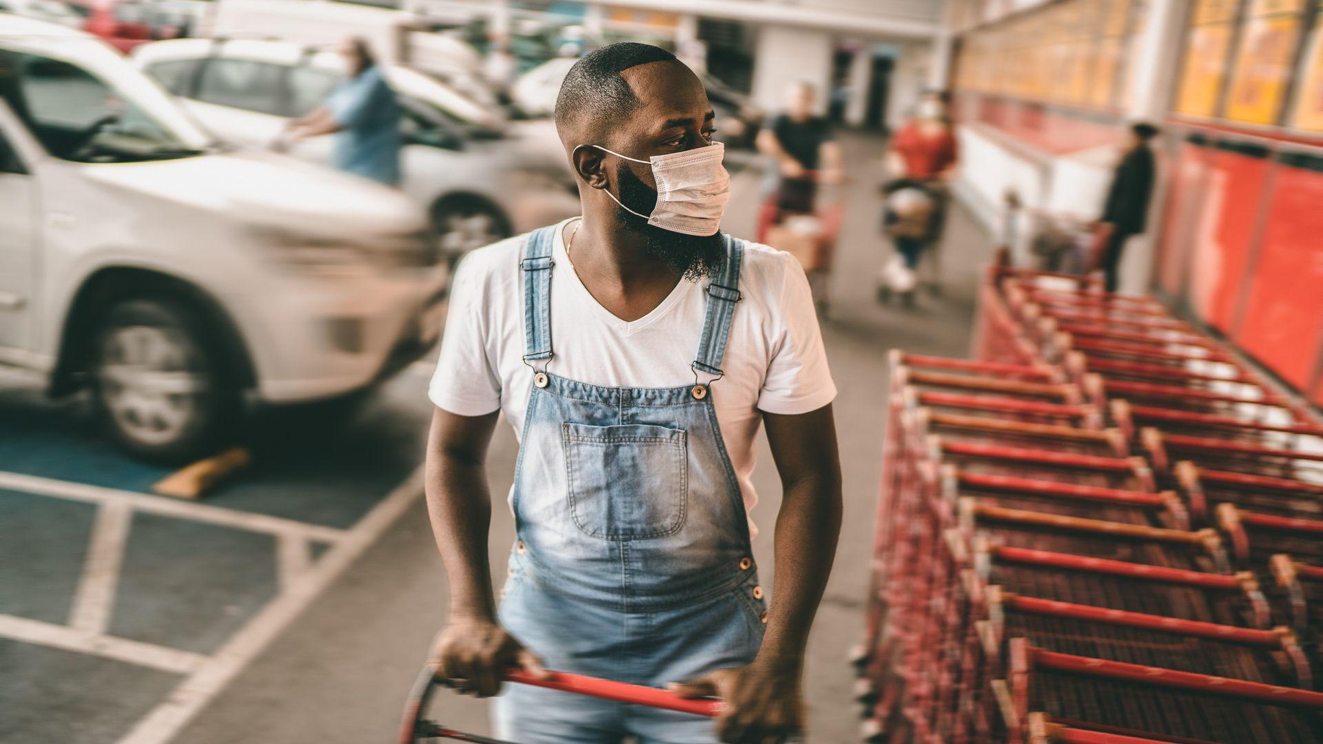 Men wearing face mask picking shopping cart in supermarket.