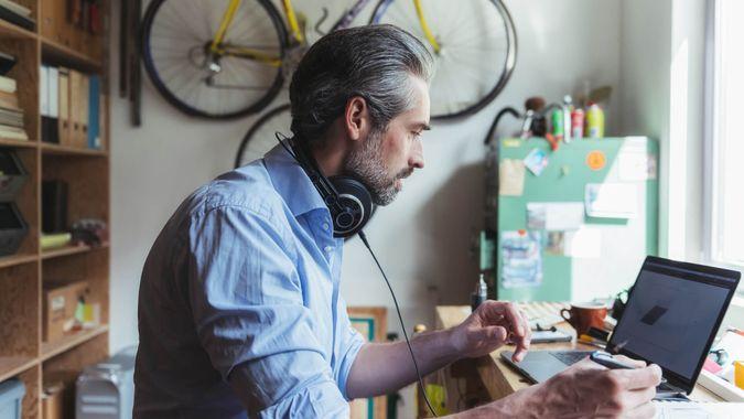 Designer with headphones working at wooden desk in home office.