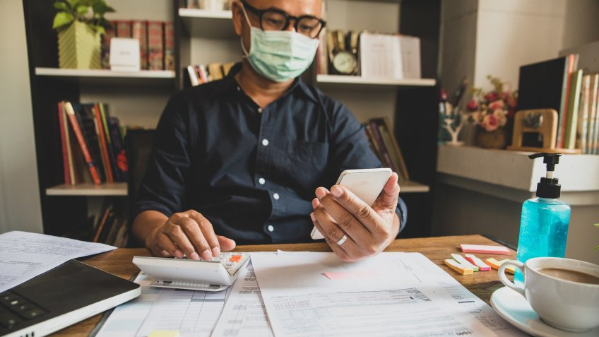 man working on taxes with coronavirus mask