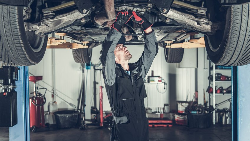 Caucasian Car Mechanic Under Vehicle Looking For Potential Issues with a Drivetrain.