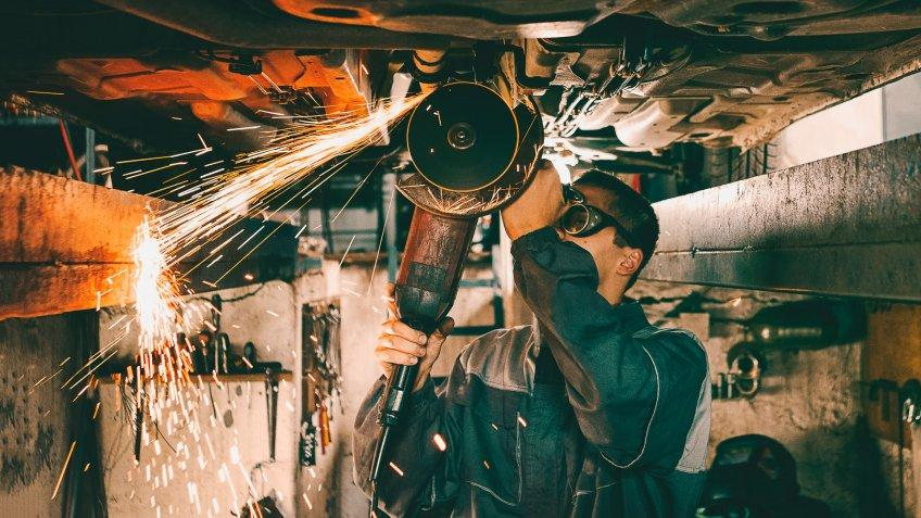 Mechanic using grinding wheel on car bottom making sparks.