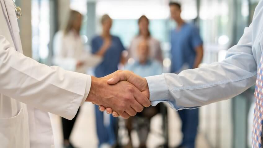 Close up of unrecognizable doctor and insurance agent handshaking - Incidental people at background.