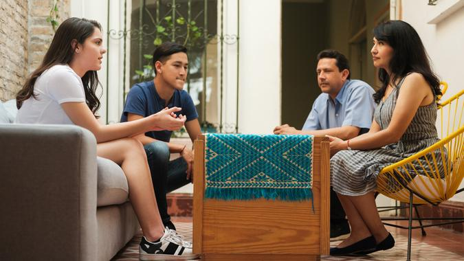Mexican mother and father sitting with their teenage children and listening to their daughter.