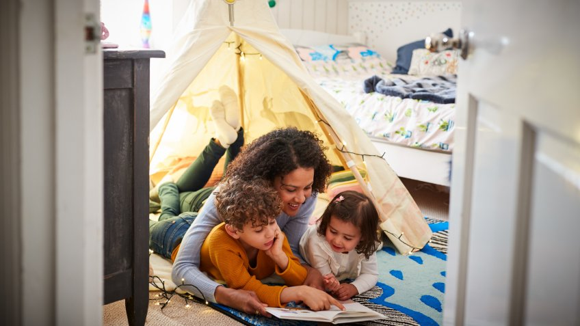 Single Mother Reading With Son And Daughter In Den In Bedroom At Home.
