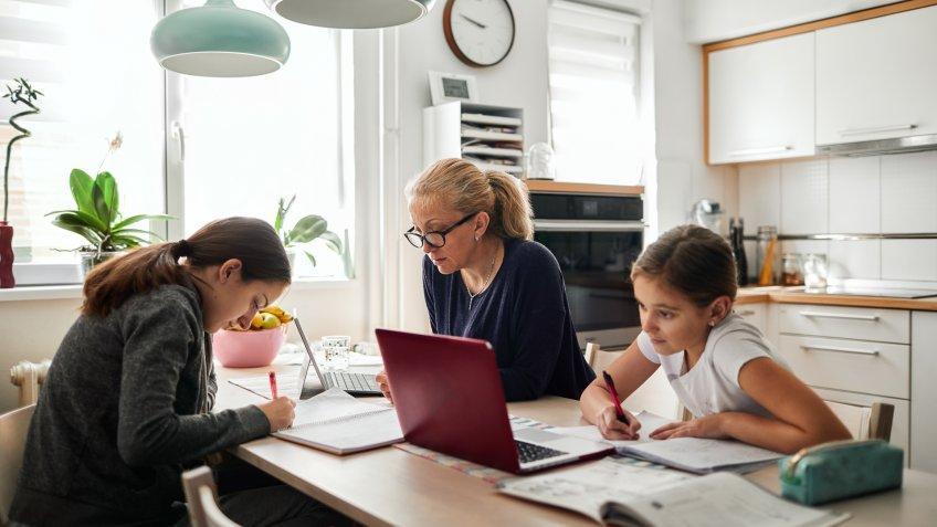 Mother helping her daughters to finish school homework during coronavirus quarantine.