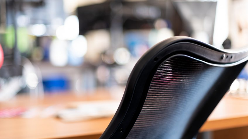 Wooden home or office room in closeup of black chair and bokeh background of computer electronics and empty space in workplace or house.