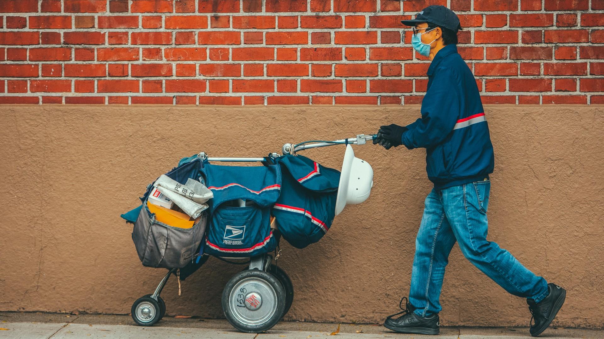 San Francisco, USA - April 4, 2020: San Francisco postal worker in mask delivering mail during stay-at-home order.