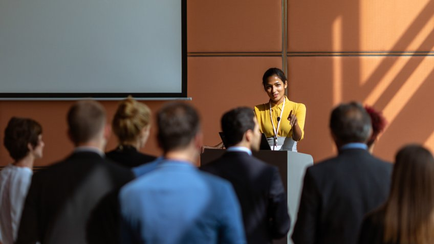 An Indian female presenter interacting with the audience at a business presentation in the board room.