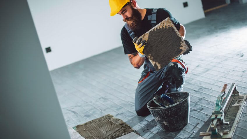 A handsome young bearded man in overalls laying a tile floor.