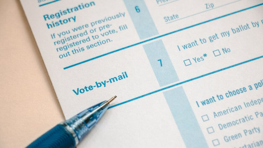 Closeup of voter registration form, focused on the Vote-by-Mail section with pencil on top.