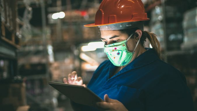 Portrait of mid adult woman wearing face mask using digital tablet - working at warehouse / industry.