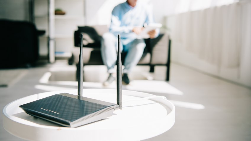 selective focus of black plugged router on white table and businessman sitting on sofa.