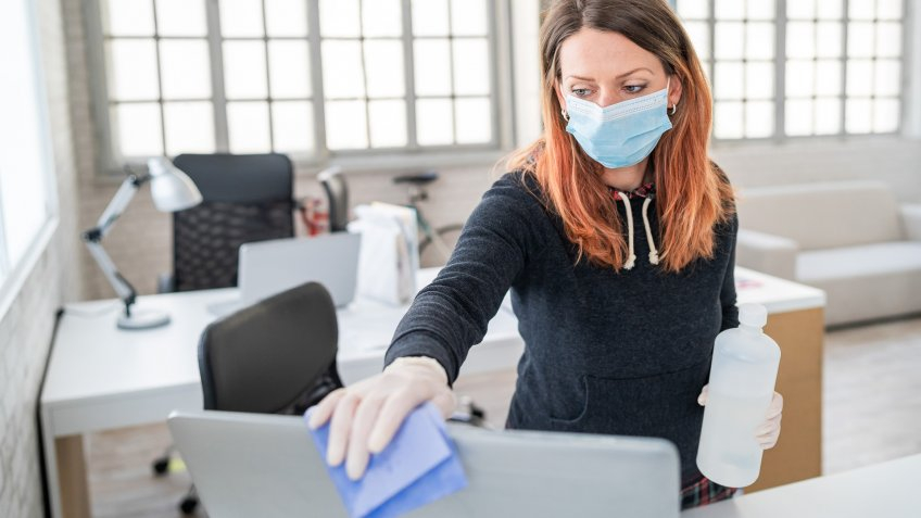 Woman in the office using disinfectant  for sanitizing monitor surface during COVID-19 pandemic.