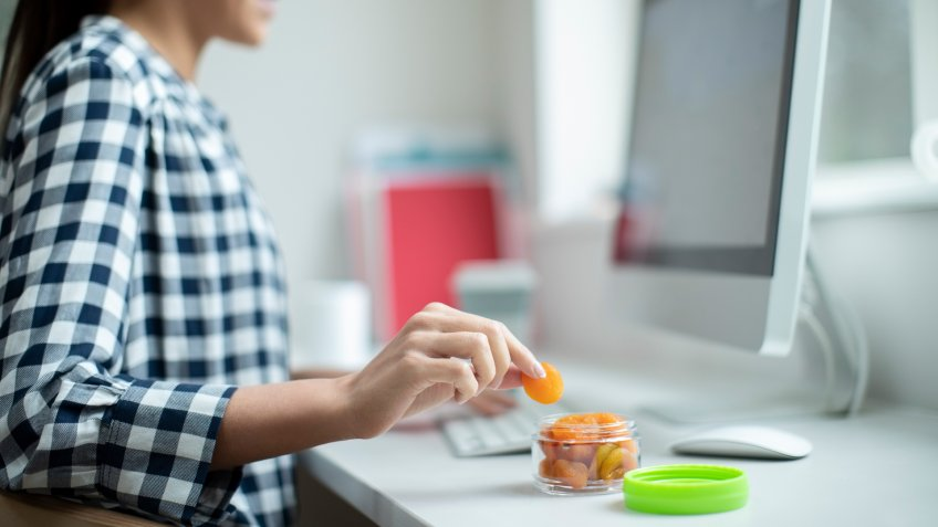 Female Worker In Office Having Healthy Snack Of Dried Apricots At Desk.