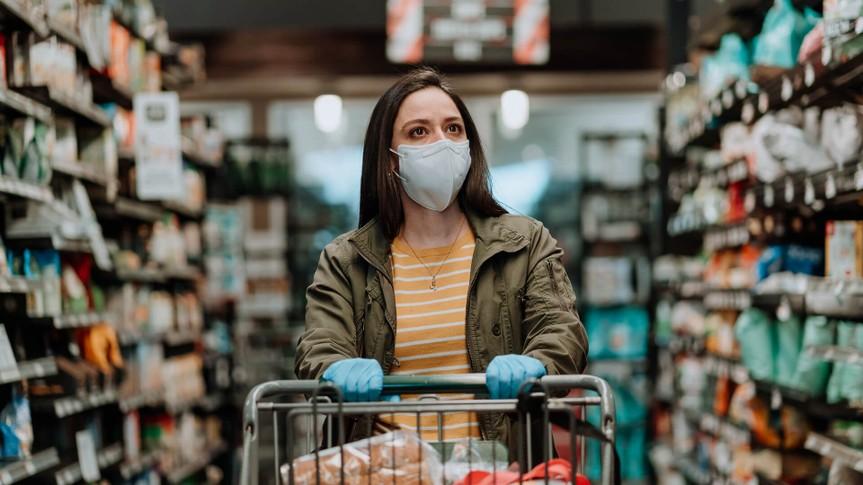 Woman pushing supermarket cart during COVID-19.