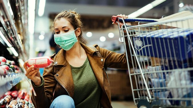 Young woman wearing protective mask and buying food in grocery store during coronavirus pandemic.