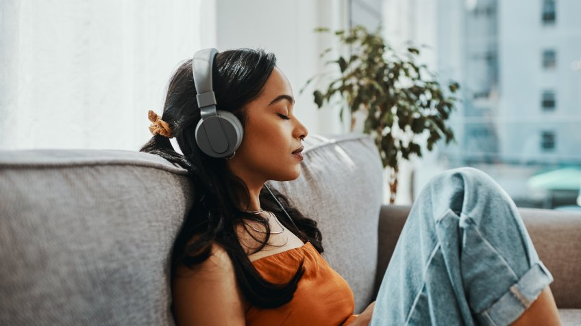 Shot of a young woman using headphones while relaxing on the sofa at home.