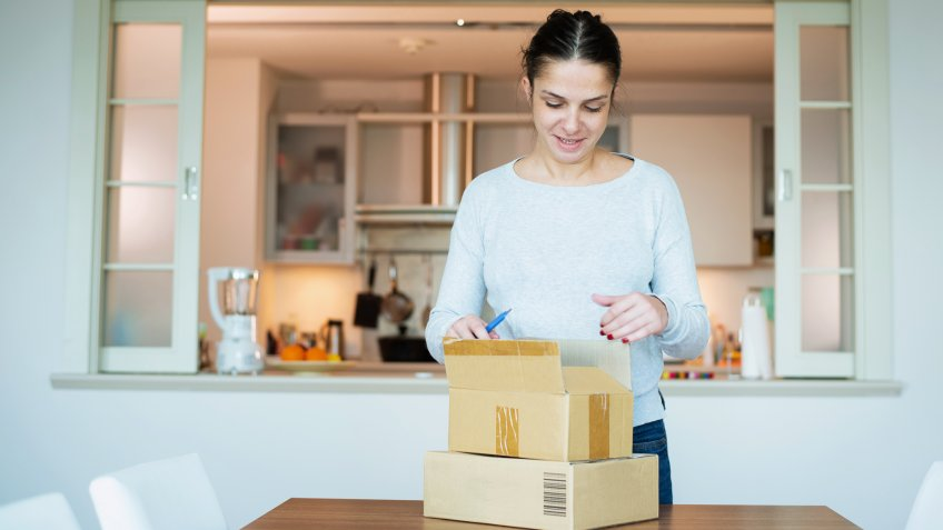 A woman opening boxes containing products she purchased online.