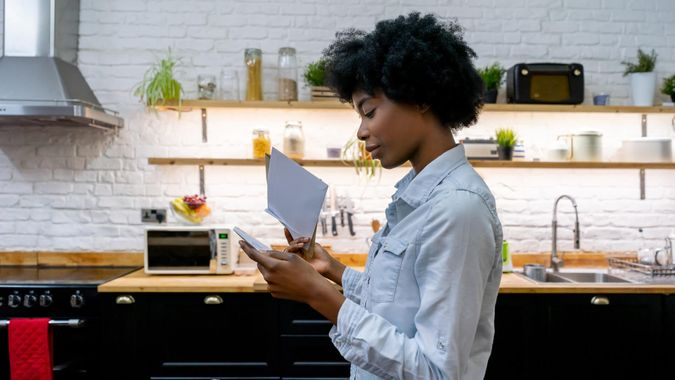 Portrait of a African American woman at home reading the mail - lifestyle concepts.