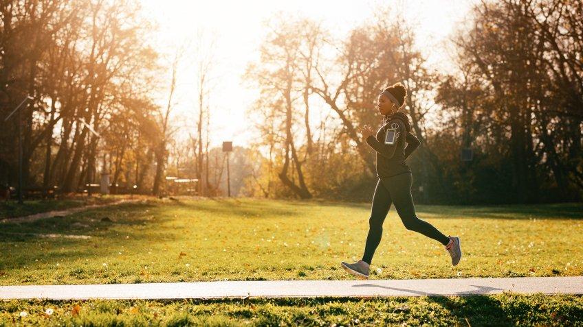 Full length of black sportswoman jogging in nature.