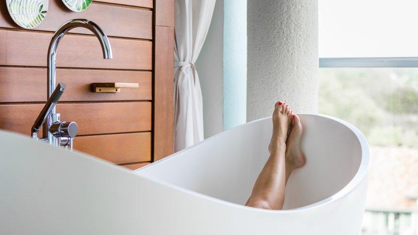 Bare feet in a luxury bathtub on a balcony.