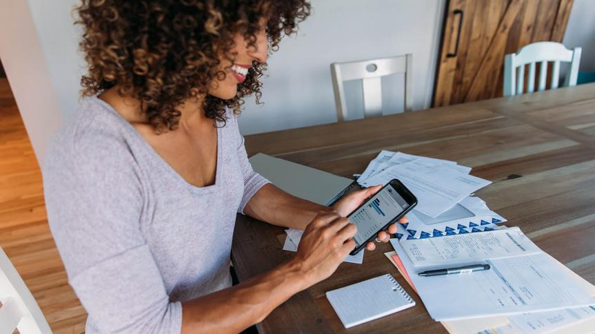A woman sits at her dining room table with laptop and financial reports doing her monthly budget.