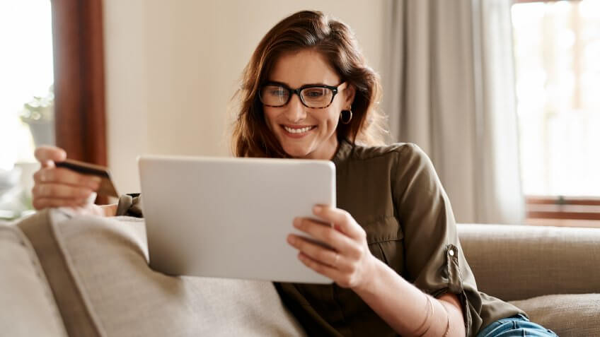 Cropped shot of an attractive young woman using a digital tablet and a credit card to shop online while sitting in her living room at home.